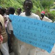 Demonstrator holding a placard calling for the return of Aristide