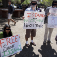 """Students hold signs stating that the, """"Number of Palestinian Political Prisoners"""