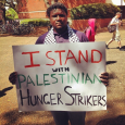 SJP member Eric Brown holds a sign in solidarity with Samer Issawi.