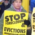 Woman holding a Stop Foreclosures and Evictions sign