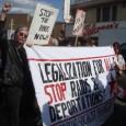 """Una pancarta: """"Alto a los redadas ahora!"""" Una otra: """"Legalizacion para todos"""""""