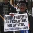 """Woman chanting and holding sign saying, """"Muhlenberg is and essential hospital."""""""